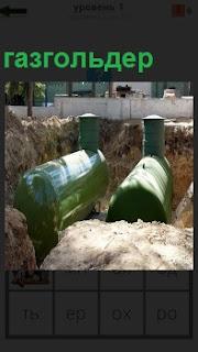 В земле выкопана яма, в которую помещены два газгольдера для хранения газа