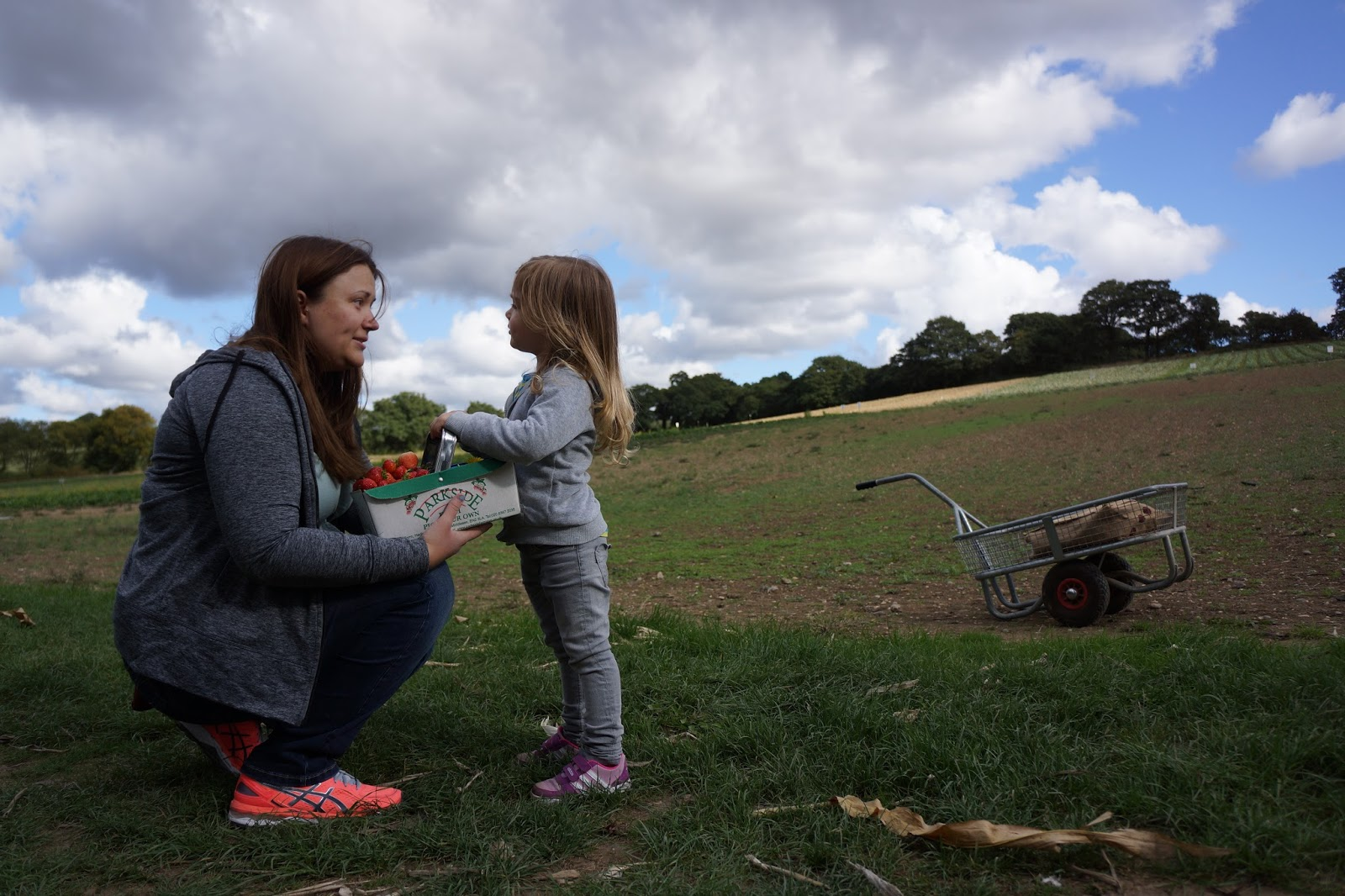 mother and toddler daughter talking to each other on a field