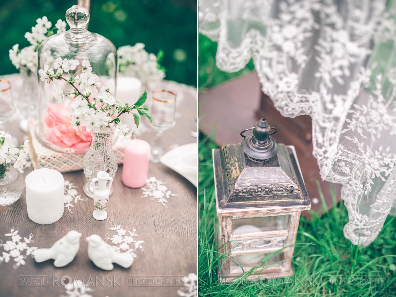 Romantyczna aranżacja stołów weselnych z koronkami w tle.