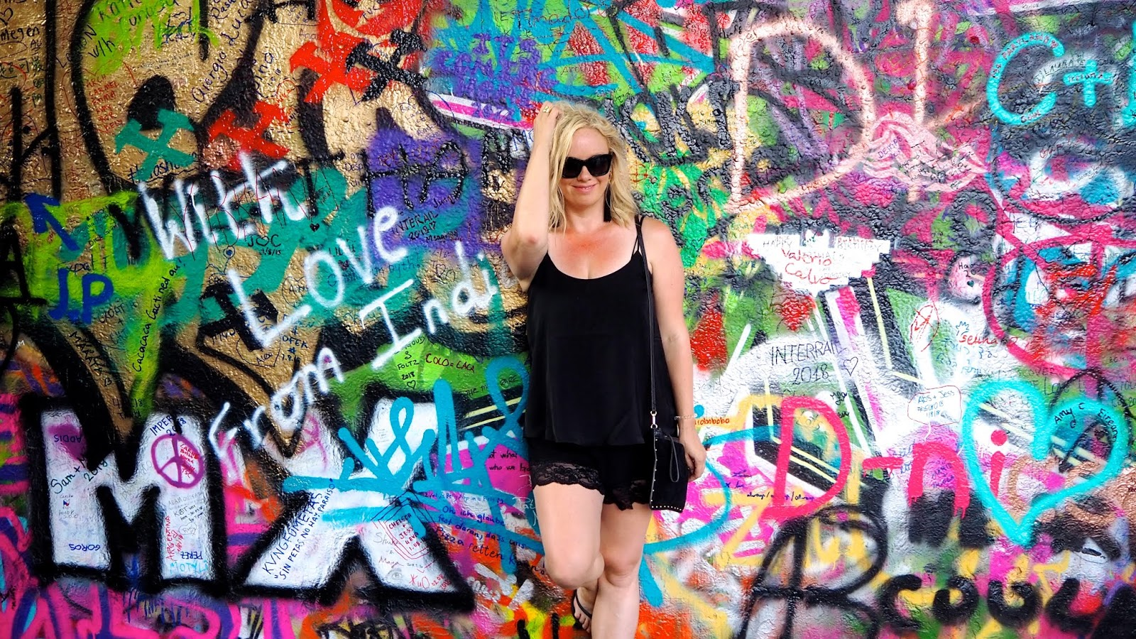 Ashley Turner with John Lennon Wall wearing lace trimmed black shorts and a black camisole