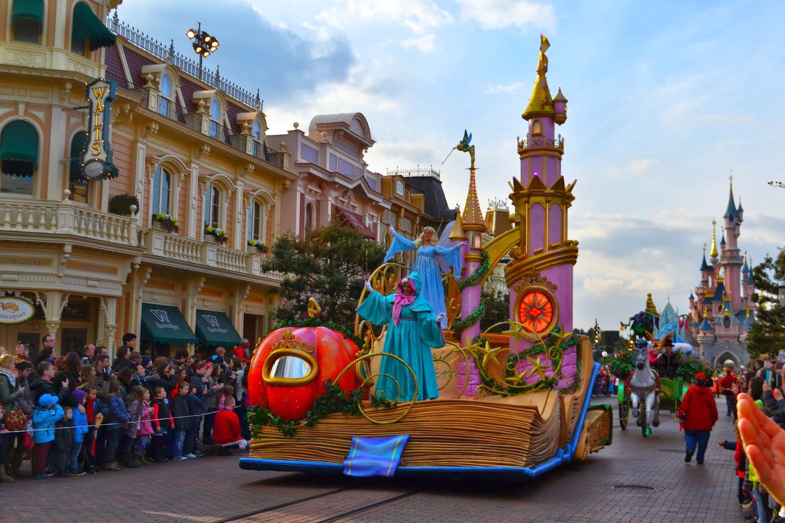 the sleeping beauty float in the Disneyland parade the fairy god mother can be seen at the front with sleeping beauty standing behind