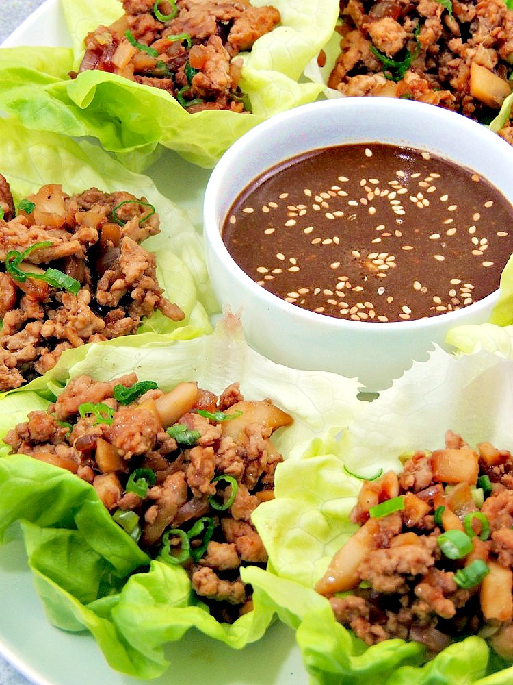 Copycat PF Chang's Chicken Lettuce Wraps on a white serving platter with dipping sauce in a white bowl.