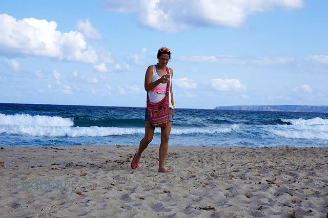 babidji qui essaie de regarder une photo sur son téléphone en grimaçant sur la plage de ses Illetes à Formentera