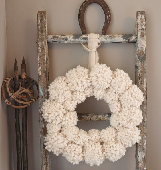Shabby chic white pompom wreath, rustic ladder, and vintage ski poles