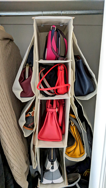 image of a multi-pocket hanging purse organizer, hanging in my front coat closet