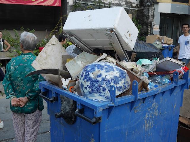broken Chinese vase in a trash bin