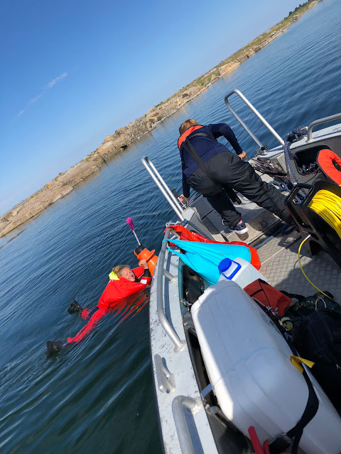 Kartoittaja kelluu pelastautumispuvussa veneen vieressä, toinen henkilö seisoo veneessä vastassa.