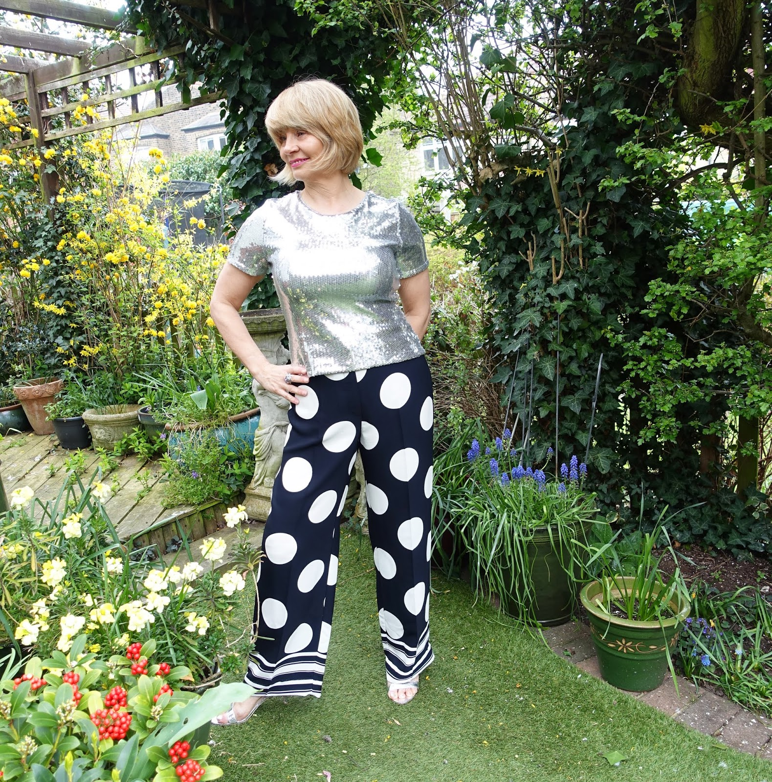 A spring garden is the setting for midlife blogger Gail Hanlon from Is This Mutton in wide statement trousers, silver sequinned top and silver naked sandals