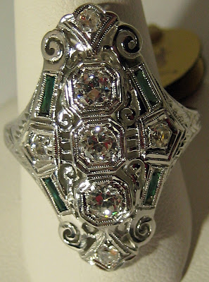 Art Deco diamond and emerald shield dinner ring.