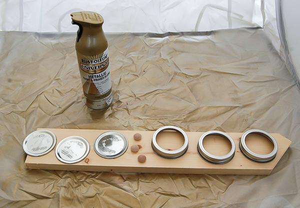 Spraying Mason Jar lids and rings with gold spray paint