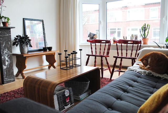 Wijd shot van een zitkamer in een bohemien sfeer met veel planten en vintage spullen.