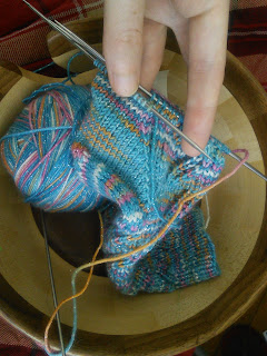 A sock live on double pointed needles.  The needles are being held in someones hand, and the sock is turned to the camera to show the line of decreases forming the gusset of the sock.