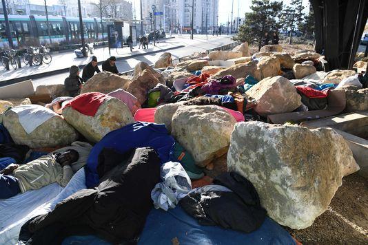 Un migrant allongé entre les blocs de pierre sous un pont du boulevard Ney, à Paris, le 15 février 2017