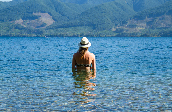 Vancouver Fashion Blogger, Alison Hutchinson, is wearing an H&M leopard print bikini and an Aritzia hat while swimming at Cowichan Lake in British Columbia