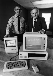 "A photograph of two men by a pair of computers, the screens reading ""True"" and ""Basic."""