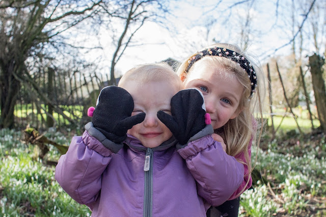 Sisters playing peekaboo behind each with a backdrop of snowdrops