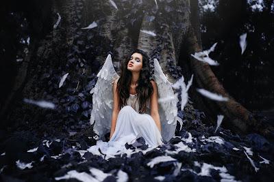 Chica con alas sentada delante de un árbol con plumas por encima