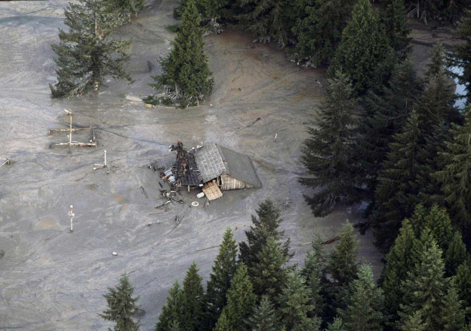 A house is submerged along the Toutle River which flooded in the aftermath of the eruption of Mount St. Helens on May 19, 1980. Area streams and rivers rose quickly as ice and snow on the volcano melted instantly.