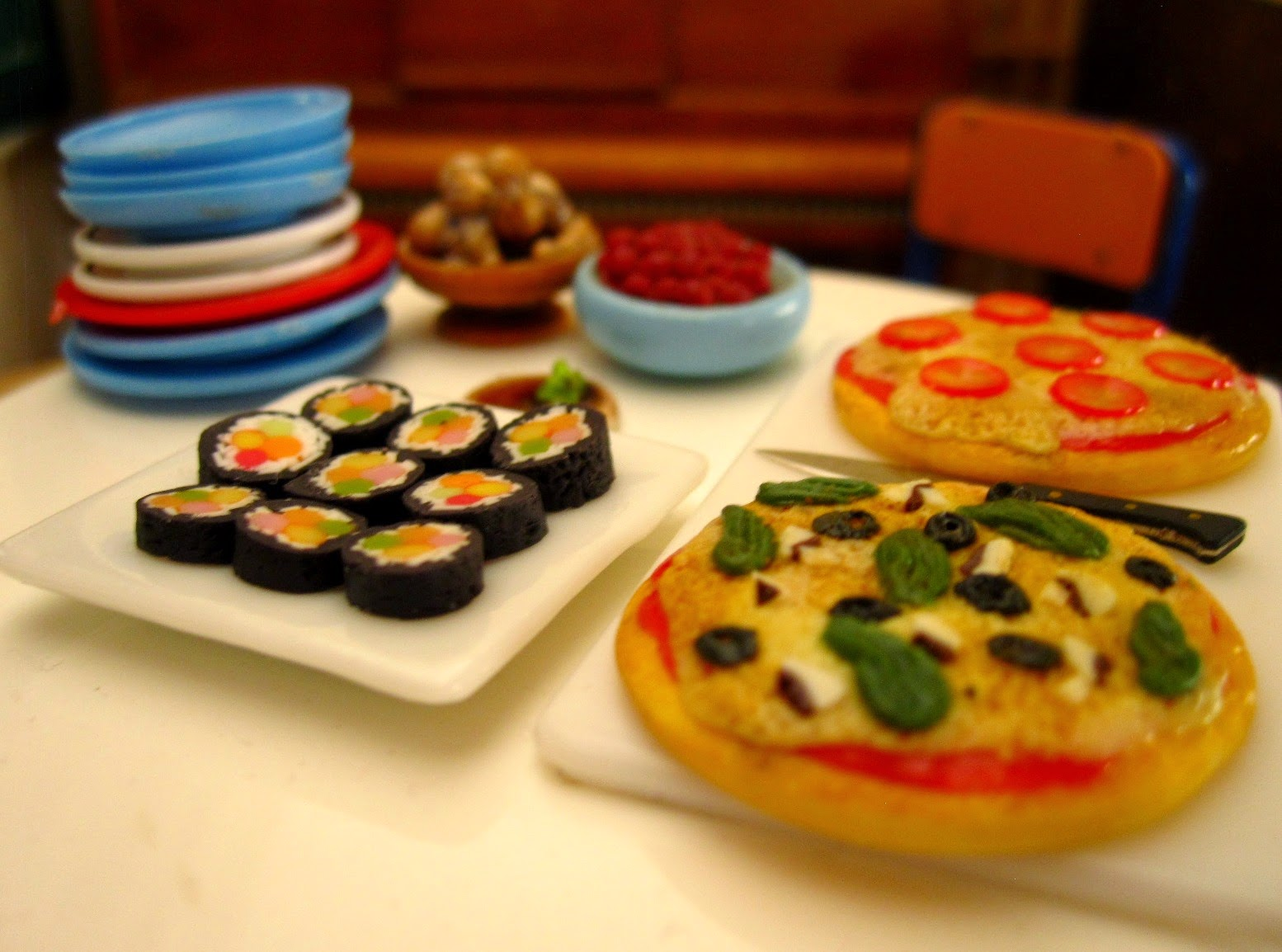 Miniature dolls' house savoury food arranged on a table, including sushi, nuts, olives and two sorts of pizza.