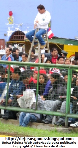 Foto de hombre peruano que llevó su escalera para poder apreciar mejor el desfile de la Gran Parada Militar por Jesus Gómez