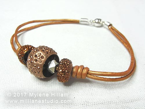 Bronze leather cord bracelet strung with bronze acrylic pave beads, secured in place by barrel knots