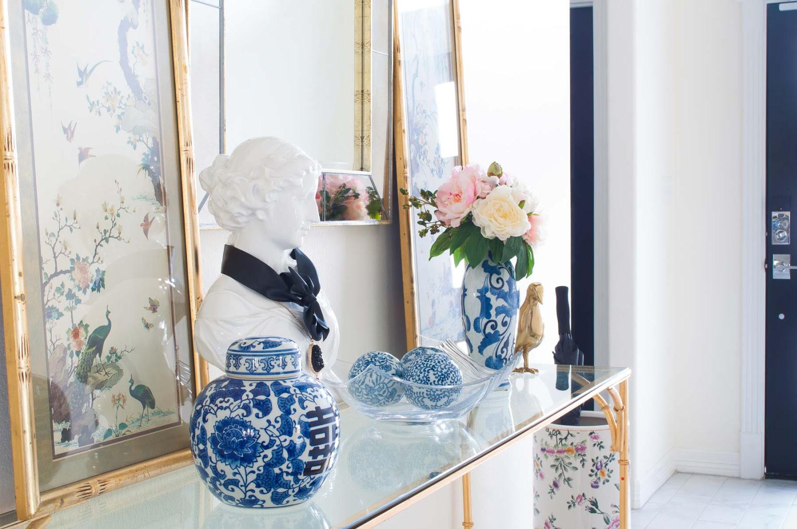 Ginger jars, vintage bamboo chinoiserie art and a stunning mirror look lovely in this black and white foyer.