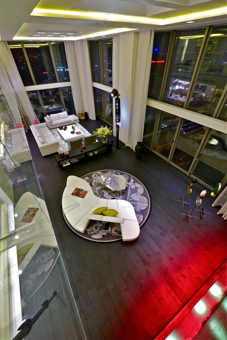 Penthouse living room at night from upper floor