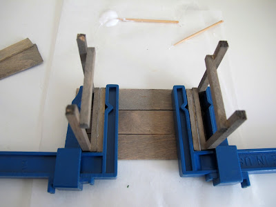 Dolls' house miniature potting table kit upside down, with legs glued on and clamped.