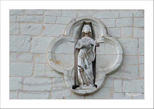 une statue blanche dans une chasse au dessus du portail de la chapelle
