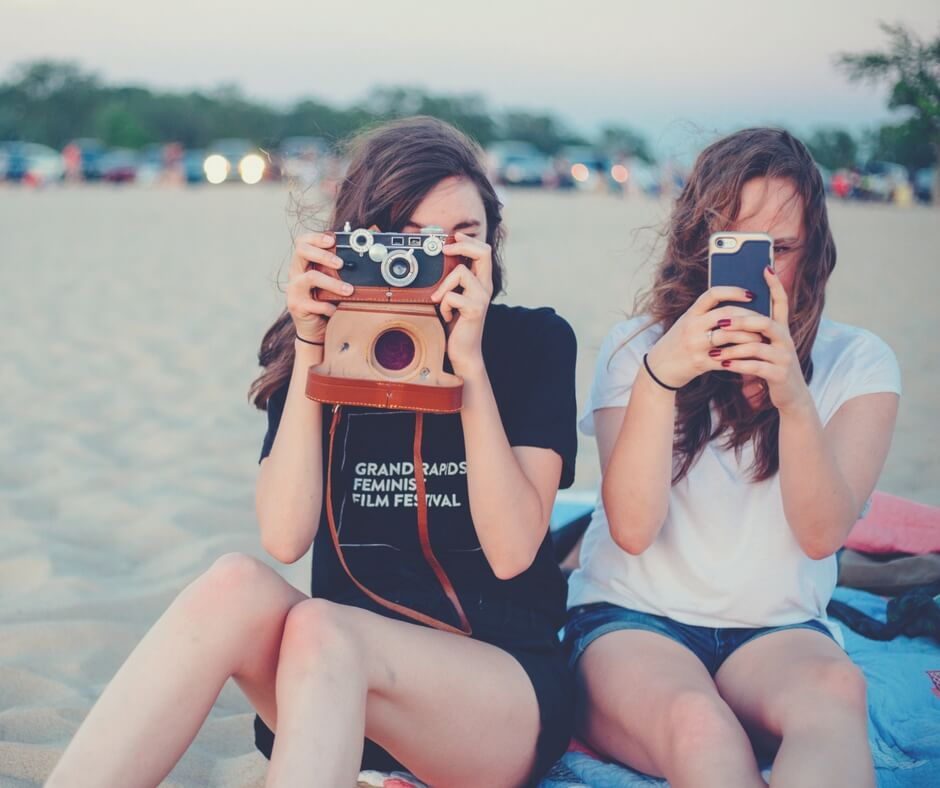 "Two teenage girls sit on a beach, they are both looking at the camera. One has a camera in front of her face, and the other has an iPhone in front of her face, they're both taking a photo of the photographer. Parked cars are blurred in the background, lining the beach. Image for ""Teaching your children about social media""."
