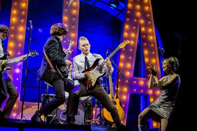 actors dressed like the beatles performing onstage