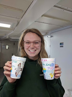 Smiling woman holds two cups with drawings on them. She holds the cups up just below her head.