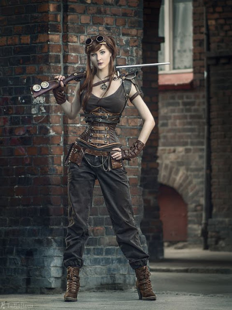 This steampunk costume is a simple mix of accessories and simple clothing elements all shades of brown. Model wears goggles, tank top, pants, harness, epaulettes, corset, belt with pouches, boots, fingerless gloves and necklace. She carries a steampunk shotgun with gauges on it.