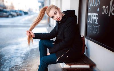 Chica rubia con coleta sentada en un banco con la calle de nieve