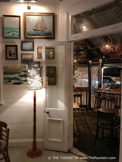 The wooden verandah of a bar with tables, chairs, paintings and decorative lights.