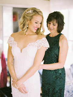 brides mother zipping up brides gown