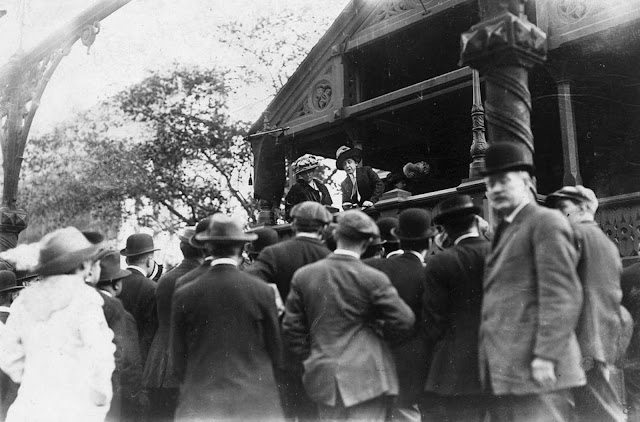 Mrs. E.R. Smith practicing speechmaking from a covered platform before a small crowd, a 'school for suffragette speakers' in Union Square.