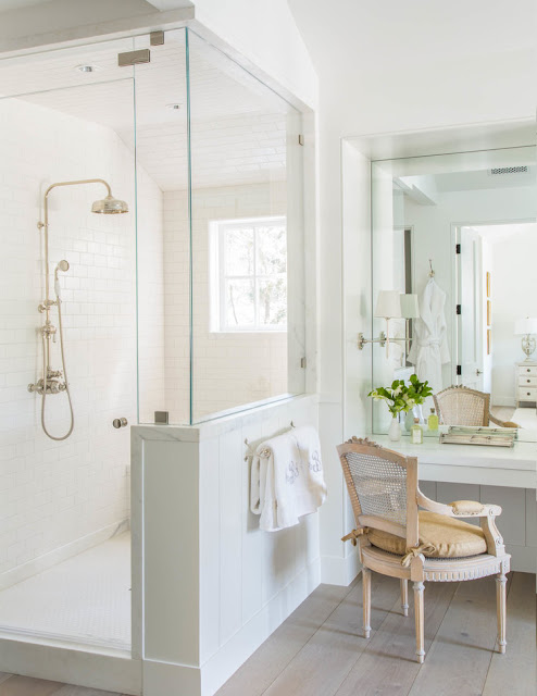 Glass walls in shower, vintage chair, and stunning bathroom design in modern farmhouse by Giannetti Home