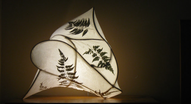 Paper light sculpture featuring ferns embedded in the shade.