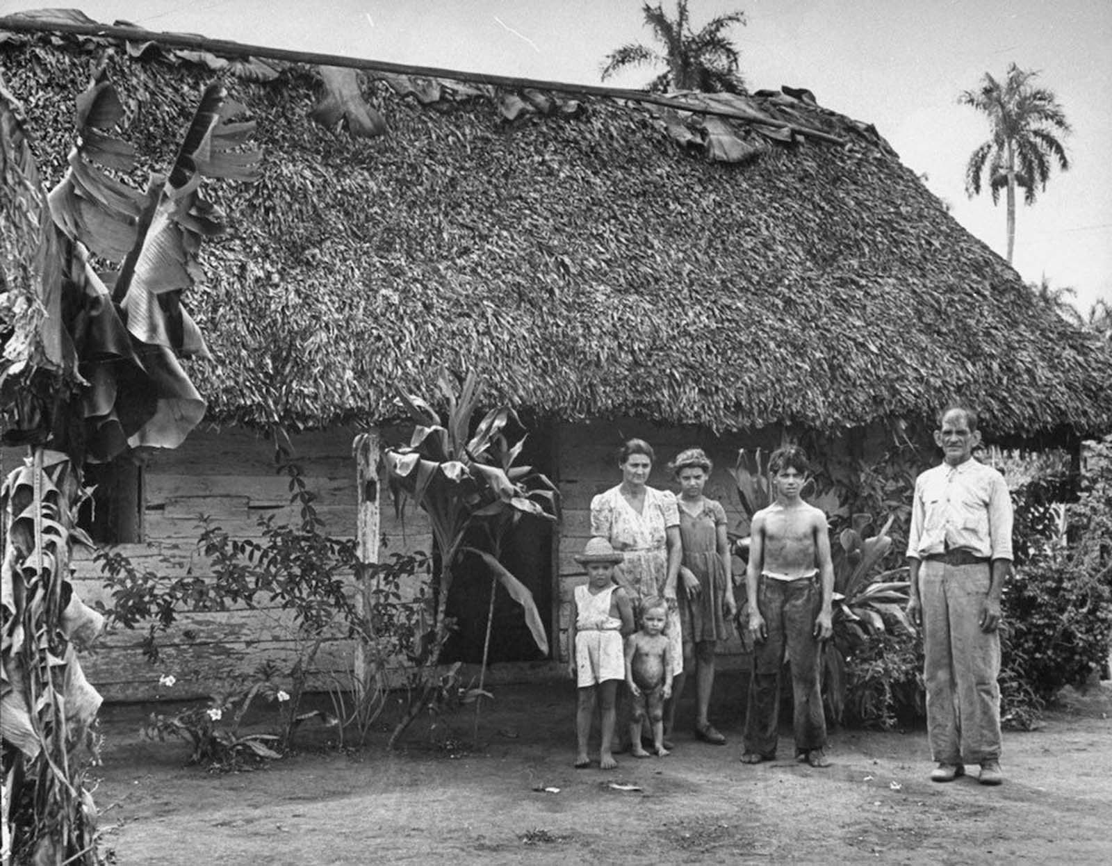 A cane cutter and his family standing in front of their home. 1944.