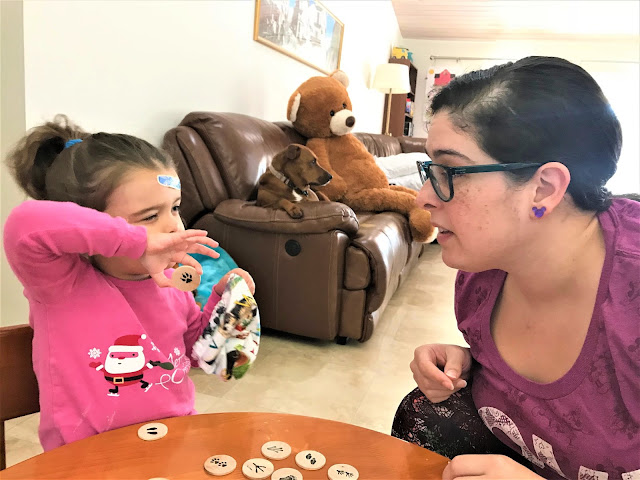 Mother and daughter sit at a small table playing an animal print matching game.