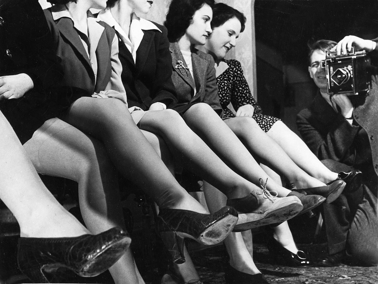 newspaper photographer with women showing nylon stockings, 1942