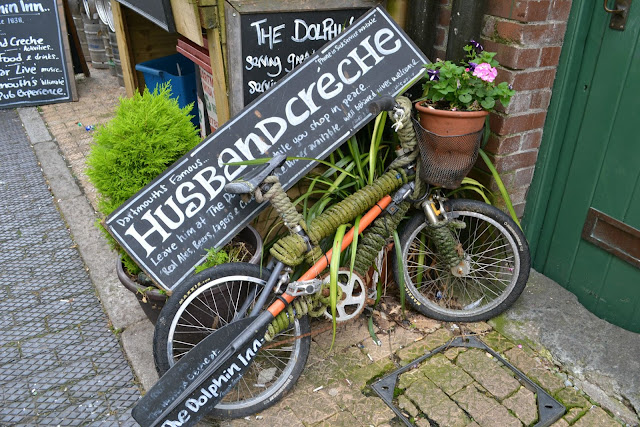 A sign on the back of a bike leant up outside a pub saying 'Husband creche'