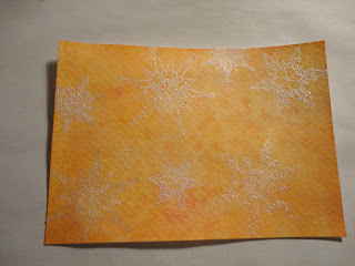 Orange salt background with snowflakes in white mica powder