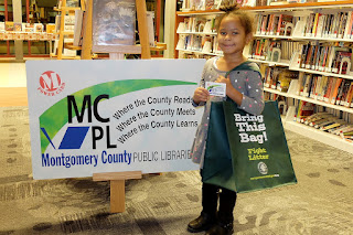 Girl next to a giant MCPL library card