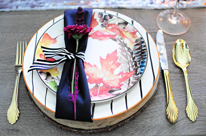 A rustic glam fall floral tablescape featuring a bold floral pumpkin centerpiece, acacia wood chargers, black and white striped dinner plates and leaf salad plates paired with vintage gold flatware. A colorful, metallic glam look perfect for any fall dining table.