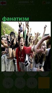 много поклонников за оградой с фанатизмом кричат и машут руками