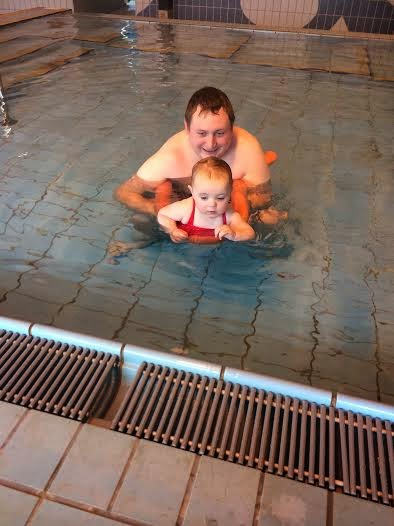 Baby Sophia swimming with a float with her dad