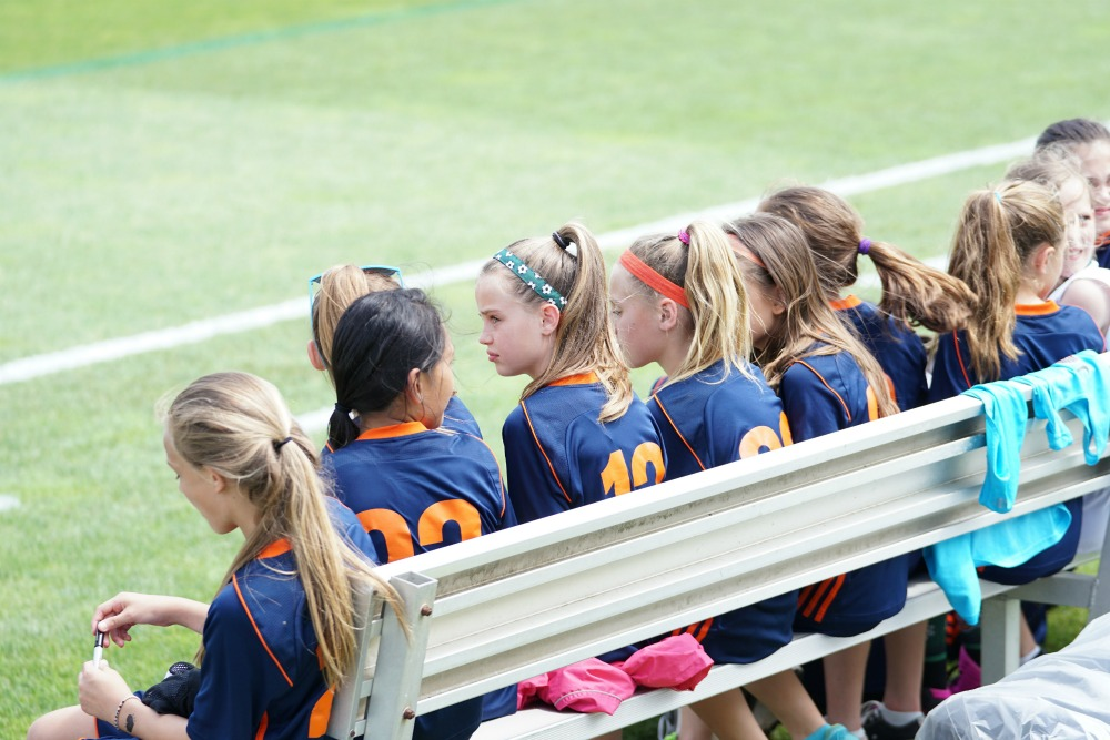 girls soccer team sitting on a bench