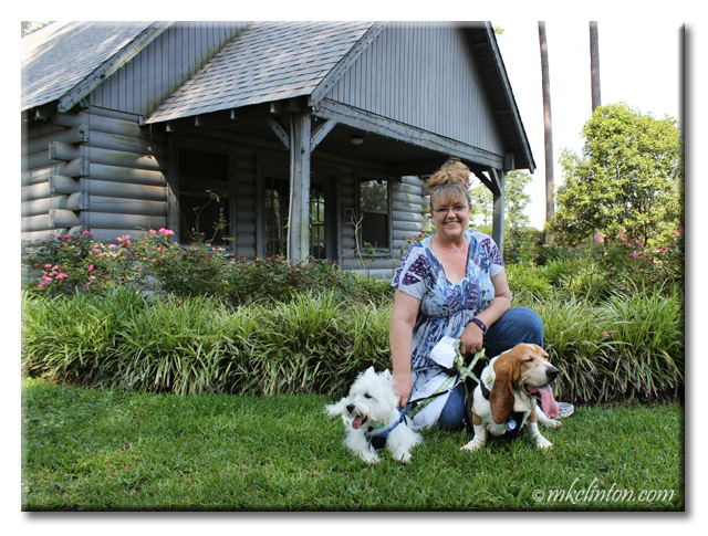 M. K. Clinton with Pierre Westie and Bentley Basset Hound posing in front of cottage
